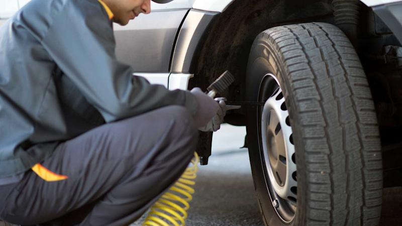 Mechanic checking the pressure of a van tyre