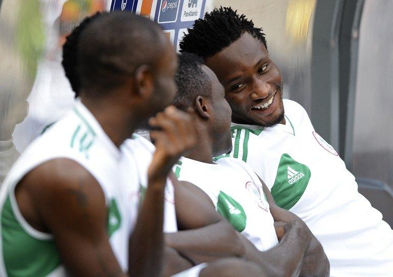 John Obi Mikel (R) shares a joke with his Nigerian team-mates as they prepare for a training session on February 9, 2013