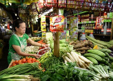 A woman arranges vegetable in a market stall in Edsa Kamias in Quezon City, metro Manila, May 23, 2018. REUTERS/Dondi Tawatao