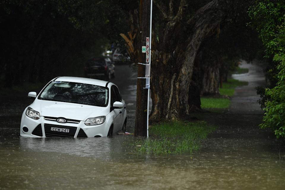 Pictured is a white car being submerged by floodwater at Marrickville.