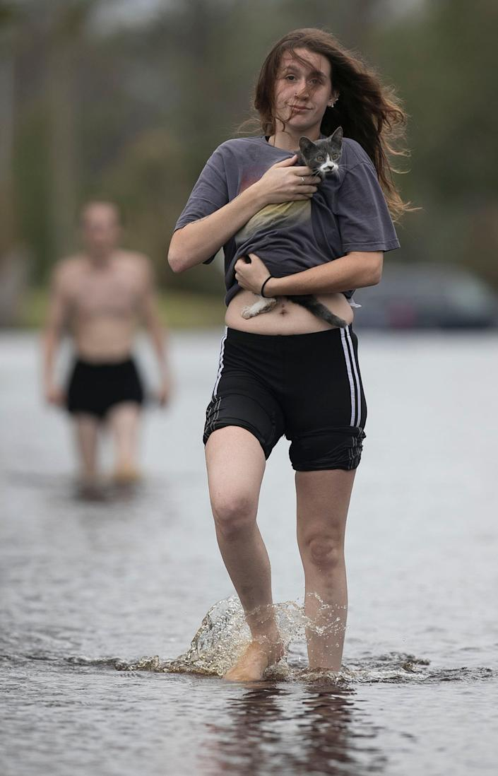 Amanda Mason on Newport, N.C. carries a cat she rescued from her neighborhood off of Nine Foot Road on Sunday afternoon, Sept. 16, 2018. Mason and her partner Zack McWilliams visited their damaged home and found the displaced cat and carried it out to safety.