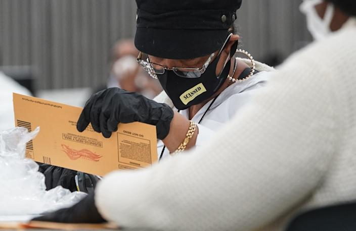 Poll workers count absentee ballots for the city of Detroit at the TCF Center in downtown Detroit on Tuesday, Nov. 3, 2020.