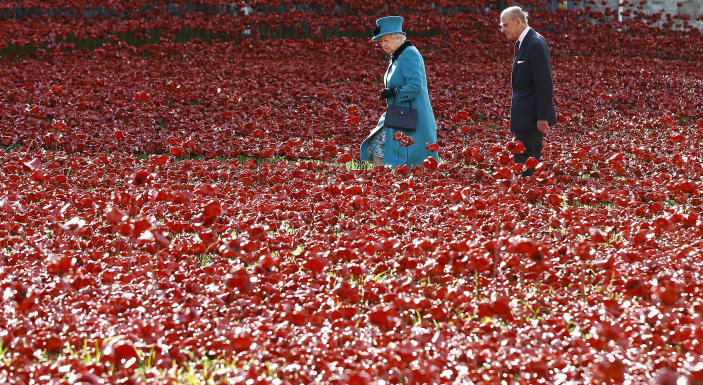 FILE - In this Oct. 16, 2014 file photo Britain's Queen Elizabeth II, left, and Prince Philip walk through the field of ceramic poppies at The Tower of London. The 99-year-old husband of Queen Elizabeth II has been hospitalized after a heart procedure. Prince Philip, the irascible and tough-minded husband of Queen Elizabeth II who spent more than seven decades supporting his wife in a role that both defined and constricted his life, has died, Buckingham Palace said Friday. He was 99. (AP Photo/Kirsty Wigglesworth, File)