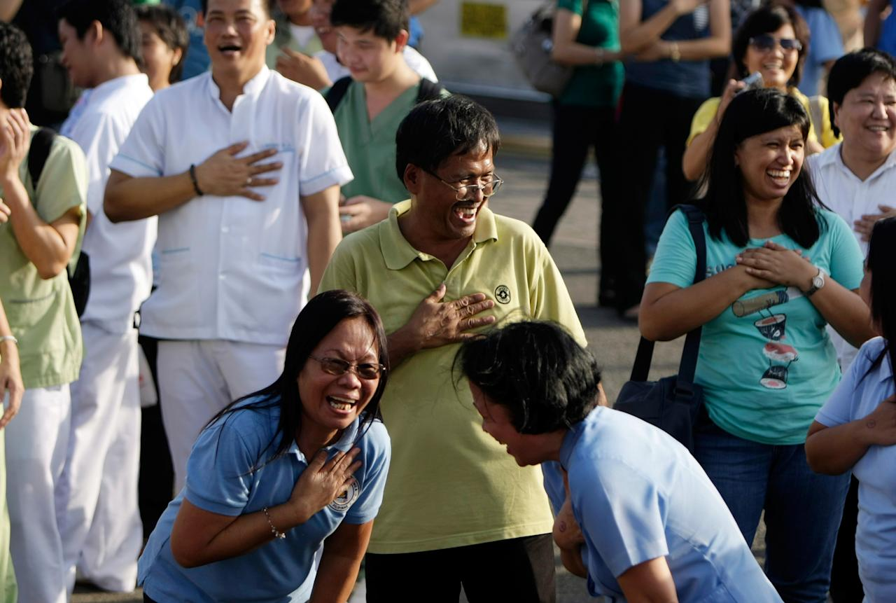 Filipinos laugh during a laughing yoga session at a park in Manila, Philippines, 21 June 2012. Participants are asked to do laughter exercises routine that combine contagious and unconditional laughter. EPA/FRANCIS R. MALASIG