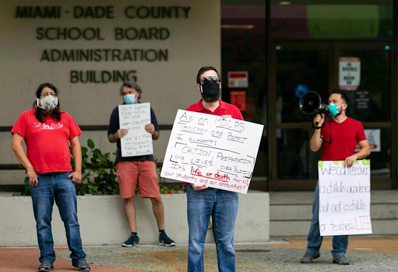 From left, teachers Charles Pilamunga, Jeff Raymond, Thomas Fiori, and Richard Ocampo participate in a rally at Miami-Dade County School Board headquarters Monday. The rally, which was led by Rank and File Educators of Miami-Dade, a faction of the United Teachers of Dade, opposed state officials pressuring school administrators to open in-person classes on Monday.