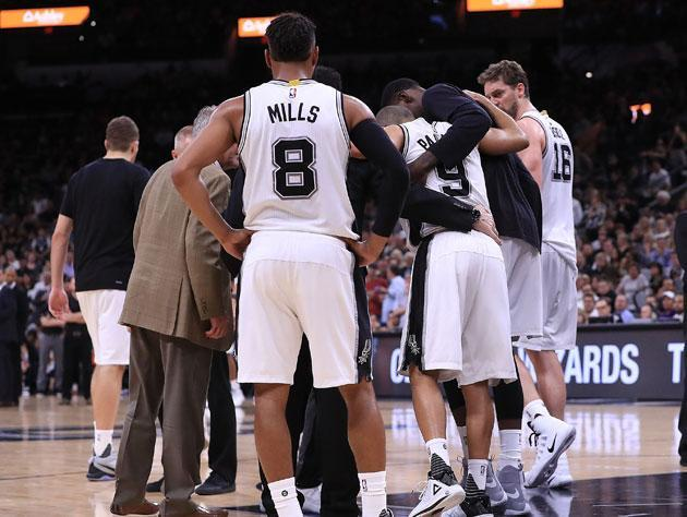"<a class=""link rapid-noclick-resp"" href=""/nba/players/4660/"" data-ylk=""slk:Patty Mills"">Patty Mills</a> and the Spurs huddle around <a class=""link rapid-noclick-resp"" href=""/nba/players/3527/"" data-ylk=""slk:Tony Parker"">Tony Parker</a>. (Getty Images)"