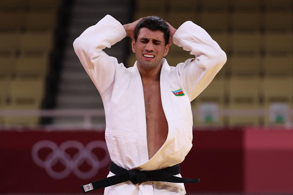 <p>Azerbaijan's Rustam Orujov (white) reacts after losing to South Korea's An Changrim in the judo men's -73kg bronze medal A bout during the Tokyo 2020 Olympic Games at the Nippon Budokan in Tokyo on July 26, 2021. (Photo by Jack GUEZ / AFP) (Photo by JACK GUEZ/AFP via Getty Images)</p>