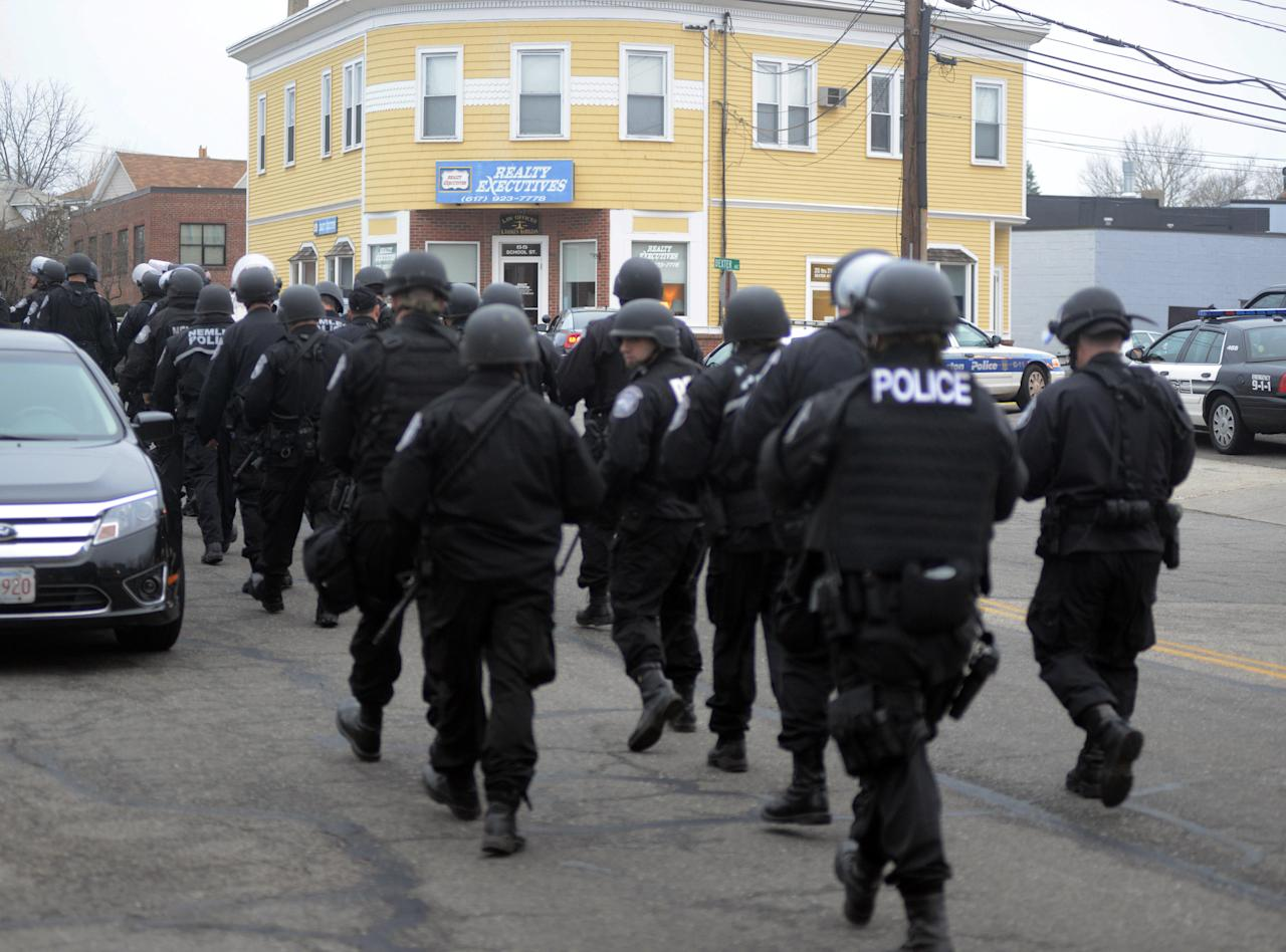 WATERTOWN, MA - APRIL 19: Police walk down School and Walnut Street on April 19, 2013 in Watertown, Massachusetts. Earlier, a Massachusetts Institute of Technology campus police officer was shot and killed at the school's campus in Cambridge. A short time later, police reported exchanging gunfire with alleged carjackers in Watertown, a city near Cambridge. According to reports, one suspect has been killed during a car chase and the police are seeking another - believed to be the same person (known as Suspect Two) wanted in connection with the deadly bombing at the Boston Marathon earlier this week. Police have confirmed that the dead assailant is Suspect One from the recently released marathon bombing photographs. (Photo by Darren McCollester/Getty Images)