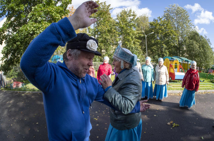 People dance near a poling station during Leningrad region's governor and municipal elections, in Luppolovo village, outside St. Petersburg, Russia, Sunday, Sept. 13, 2020. Leningrad region is the territory surrounding St. Petersburg. Elections are being held to choose governors and legislators in about half of Russia's regions. (AP Photo/Dmitri Lovetsky)