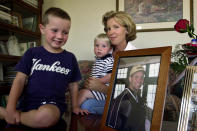 FILE - In this Sept. 16, 2001 file photo, David Beamer, his brother, Andrew, and his mother, Lisa, pose for a photo in their Cranbury, N.J. home. Lisa's husband Todd Beamer, in picture at right, was the passenger aboard the United Airlines Flight 93, who led other passengers to take action against hijackers, according to an operator who talked to Beamer just before the plane crashed in a field in western Pennsylvania on Sept. 11. (AP Photo/Brian Branch-Price, File)