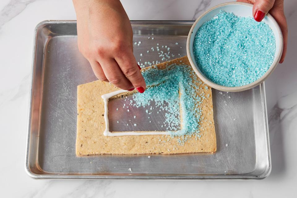Photo C: On wall B1, light blue crunchy sugar is loaded onto piped Royal Icing quickly before the icing dries.
