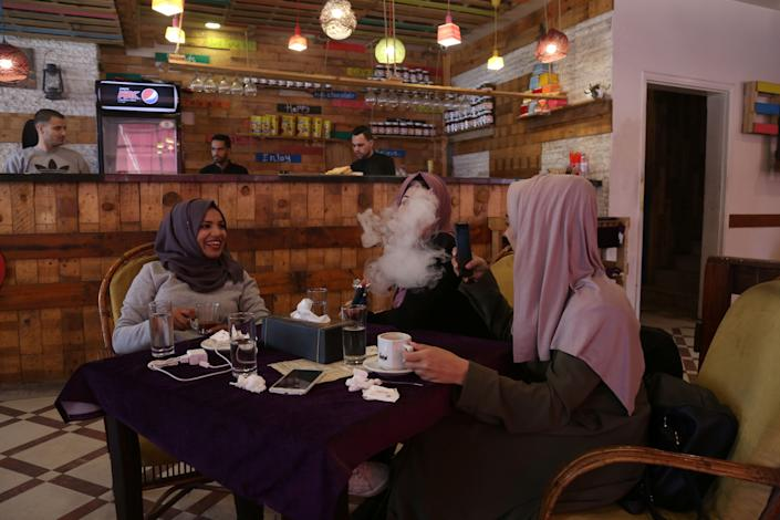 Saly Abu Amra, left, 23, a student majoring in Sharia Law, looks on as her friend smokes a water pipe at a cafe in Gaza City on Dec. 4, 2018. (Photo: Samar Abo Elouf/Reuters)