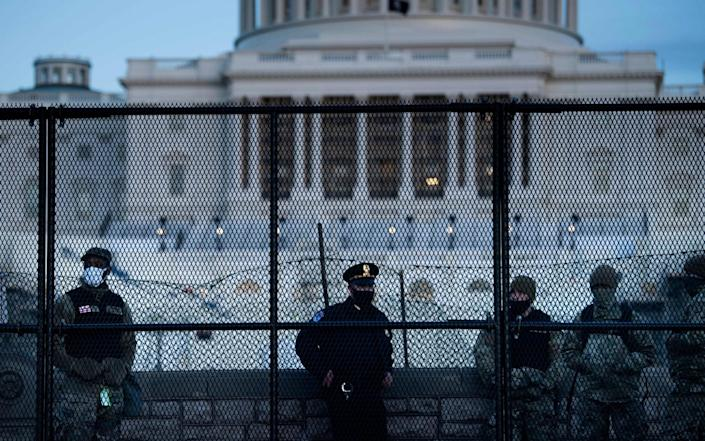 A Capitol Police officer stands with members of the National Guard - Brendan Smialowski/AFP