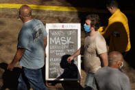 Visitors wearing face masks walk past a sign requiring masks at a restaurant along the River Walk, Wednesday, March 3, 2021, in San Antonio. Gov. Greg Abbott says Texas is lifting a mask mandate and lifting business capacity limits next week. (AP Photo/Eric Gay)