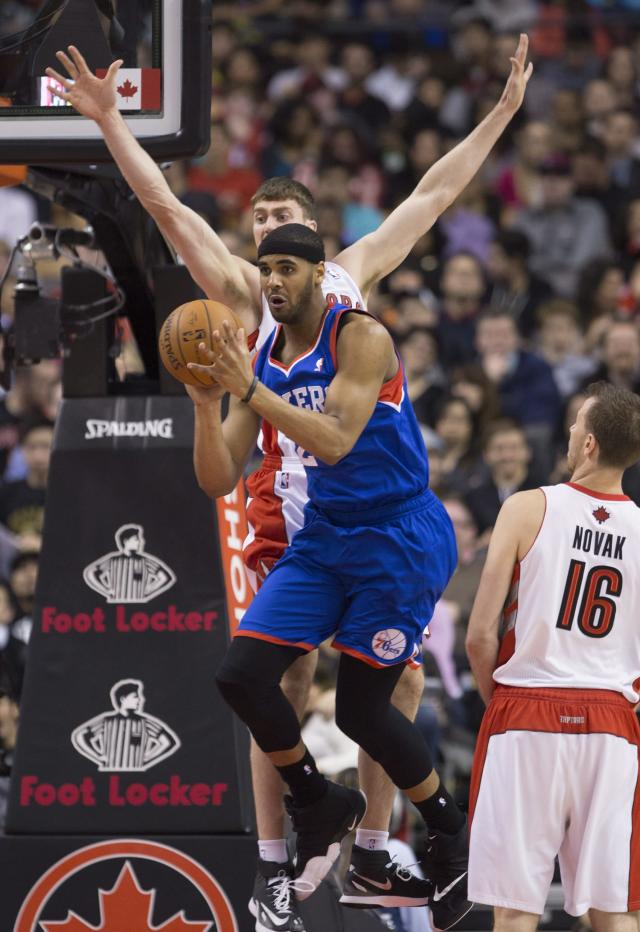 Philadelphia 76ers forward Brandon Davies (20) looks to pass as Toronto Raptors forward Tyler Hansbrough (50) defends during first half NBA action in Toronto on Wednesday, April 9, 2014. (AP Photo/The Canadian Press, Peter Power)