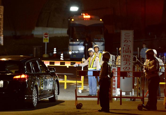 Security guard check an entering car as police officers are stationed as backup at the gate of Ohi nuclear power plant in Ohi town, Fukui prefecture, western Japan, Wednesday night, July 18, 2012. The No. 4 reactor at the plant went online Wednesday, the second to restart after the Fukushima nuclear disasters. The No. 3 reactor at the same plant was restarted earlier this month. (AP Photo/Kyodo News) JAPAN OUT, MANDATORY CREDIT, NO LICENSING IN CHINA, HONG KONG, JAPAN, SOUTH KOREA AND FRANCE