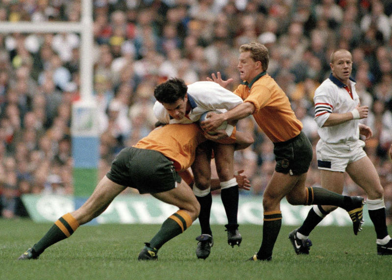 FILE - In this Nov. 2, 1991 file photo, England's Will Carling, center, is tackled by Australia's Michael Lynagh, right, during the Rugby World Cup final at Twickenham, London. England will play Australia in the 2019 Rugby World Cup quarterfinal match on Saturday Oct. 18, 2019. (AP Photo/Dave Caulkin, file)