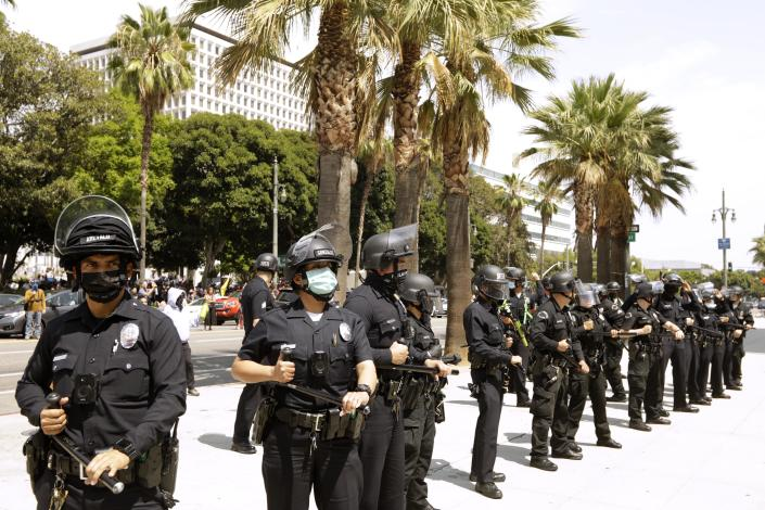 Los Angeles police officers stand by after advocates against vaccine mandates and pro-vaccine advocates confronted each other in front of City Hall in downtown Los Angeles on Aug. 14, 2021.