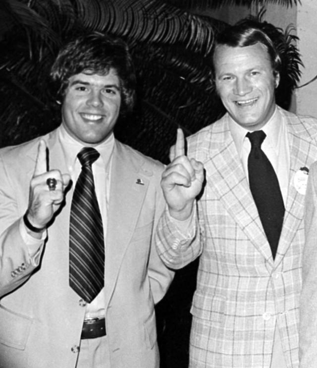 "FILE - In this Jan. 2, 1976 file photo, University of Oklahoma football coach Barry Switzer, right, and quarterback Steven Davis, give the ""number one"" sign in Miami Beach, after the Associated Press named the Sooners as the national champions for the second year in a row. A University of Oklahoma official says the starting quarterback for Oklahoma's national championship teams in 1974 and 1975 is one of two men killed when a small plane slammed into a house in northern Indiana. St. Joseph County Coroner Randy Magdalinski identified the victims of Sunday's March 17, 2013 crash as 60-year-old Steven Davis and 58-year-old Wesley Caves, both of Tulsa, Okla. (AP Photo, File)"