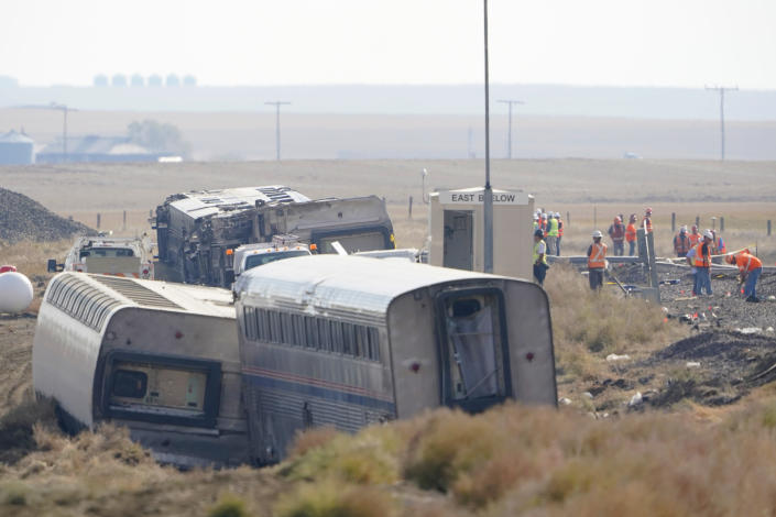 Workers stand near train tracks, Monday, Sept. 27, 2021, next to overturned cars from an Amtrak train that derailed Saturday, near Joplin, Mont., killing three people and injuring others. Federal investigators are seeking the cause of the derailment. (AP Photo/Ted S. Warren)
