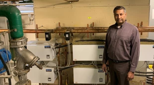Alberta Infrastructure Minister Prasad Panda stands near the electric heating system in the Old Court of Appeal building in Calgary. According to the provincial government, it will soon to be replaced by high efficiency boilers.