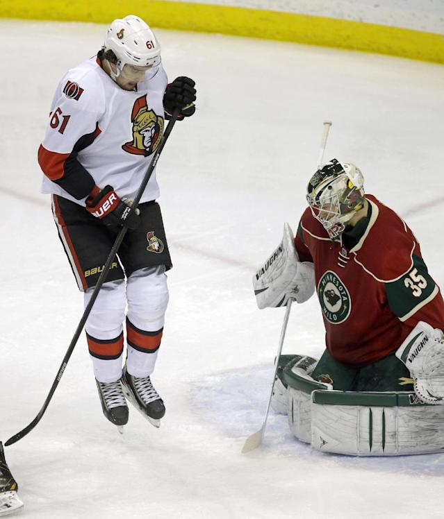 Ottawa Senators' Mark Stone, left, jumps clear for a shot on Minnesota Wild goalie Darcy Kuemper in the first period of an NHL hockey game, Tuesday, Jan. 14, 2014, in St. Paul, Minn. (AP Photo/Jim Mone)