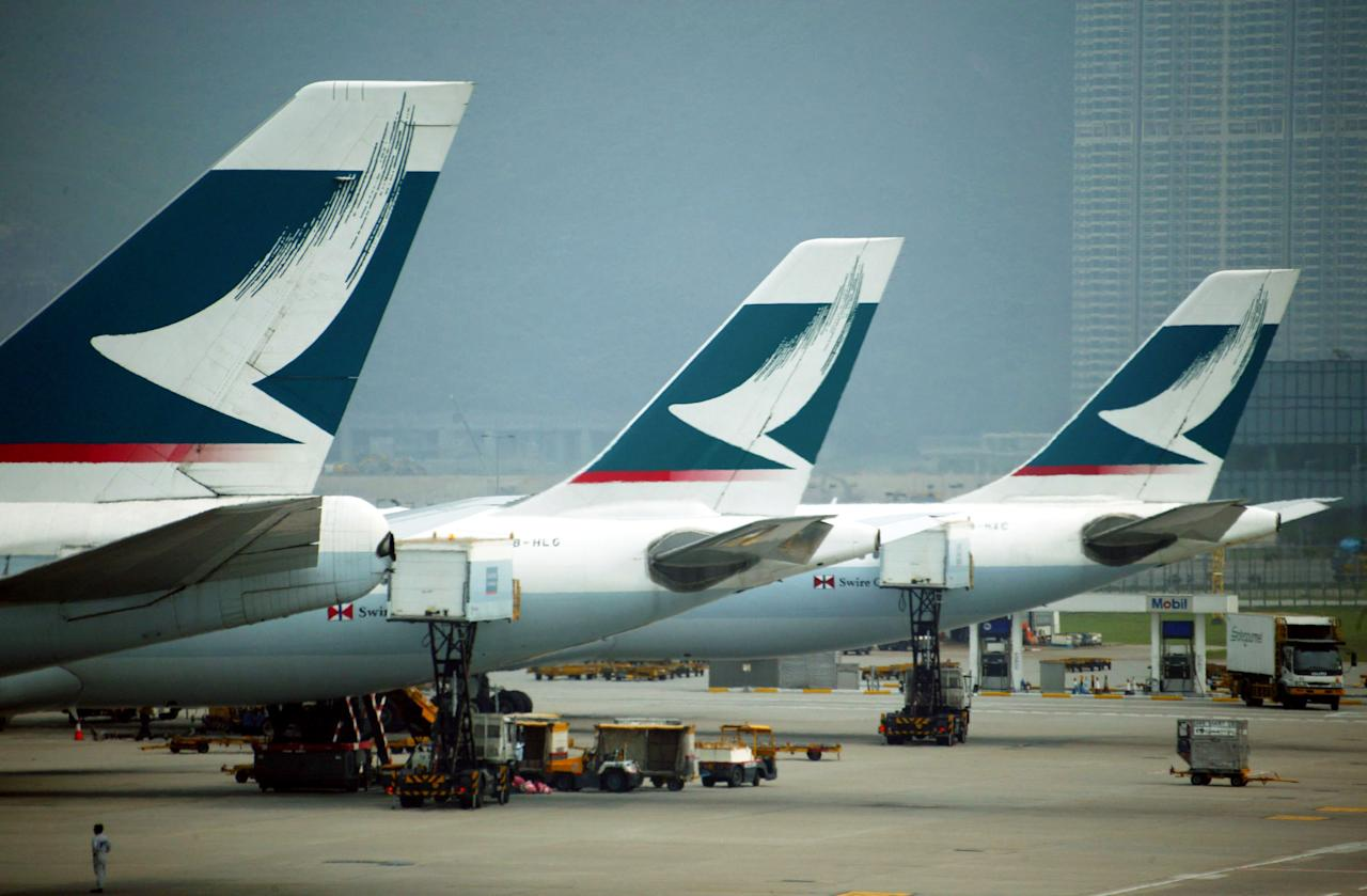 HONG KONG ? APRIL 16:  Cathay Pacific airplanes stand on the tarmac of Chek Lap Kok airport April 16, 2003 in Hong Kong, China. Cathay Pacific Airways have cut their flights as a result of flying around 60% less passengers due to the SARS virus. Cathay Pacific along with other airlines will start to measure departing passenger's temperature's starting from the 17th April, arriving passenger's temperatures will be checked in the coming days. The government today announced an increase of 36 patients to 1268 persons infected with (SARS). Total deaths have risen to 61.  (Photo by Christian Keenan/Getty Images)