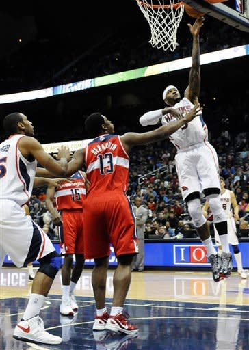 Atlanta Hawks' Josh Smith, right, shoots over Washington Wizards' Kevin Seraphin (13) and Jordan Crawford (15) in the first half of an NBA basketball game at Philips Arena in Atlanta, Wednesday, Nov. 21, 2012. (AP Photo/David Tulis)