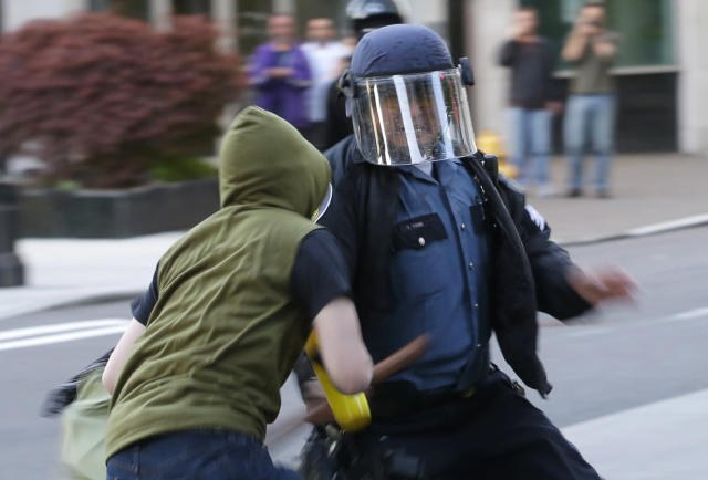 A Seattle Police officer shoves his baton at a protester during a May Day march that began as an anti-capitalism protest and turned into demonstrators clashing with police, Wednesday, May 1, 2013, in downtown Seattle. (AP Photo/Ted S. Warren)