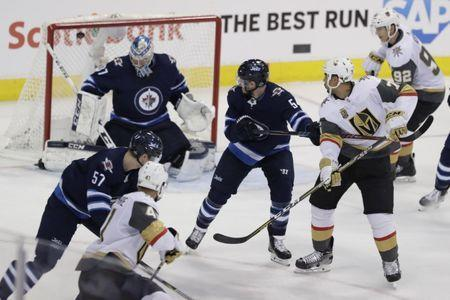 May 20, 2018; Winnipeg, Manitoba, CAN; Vegas Golden Knights right wing Ryan Reaves (75) tips the puck to score a goal past Winnipeg Jets goaltender Connor Hellebuyck (37) in the second period in game five of the Western Conference Final of the 2018 Stanley Cup Playoffs at Bell MTS Centre. Mandatory Credit: James Carey Lauder-USA TODAY Sports