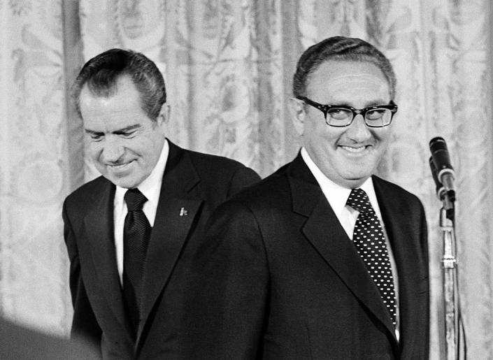 Henry Kissinger stands before a microphone in front of Richard Nixon.