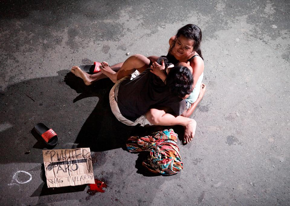 FILE PHOTO: A woman cradles the body of her husband, who was killed on a street by a vigilante group, according to police, in a spate of drug-related killings in Pasay City on July 23, 2016. (Source: REUTERS/Czar Dancel)