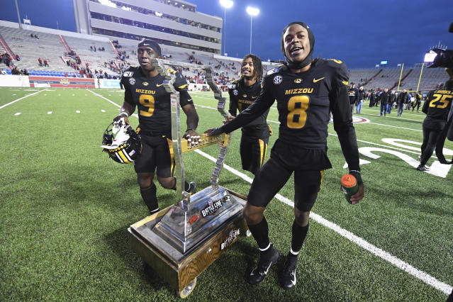 Missouri's Tyree Gillespie (9), Adam Sparks (14) and Jarvis Ware (8) celebrate as they wheel off the Battle Line trophy after Missouri defeated Arkansas 24-14 during an NCAA college football game Friday, Nov. 29, 2019, in Little Rock, Ark. (AP Photo/Michael Woods)
