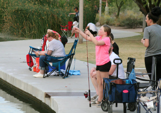 In this April 30, 2020 photo, a girl checks her line as people fish at Veterans Oasis Park in Chandler, Ariz. Many state fishing programs have continued to stock community lakes during the coronavirus pandemic, allowing people who have been locked up for weeks a chance to enjoy the outdoors. (AP Photo/John Marshall)