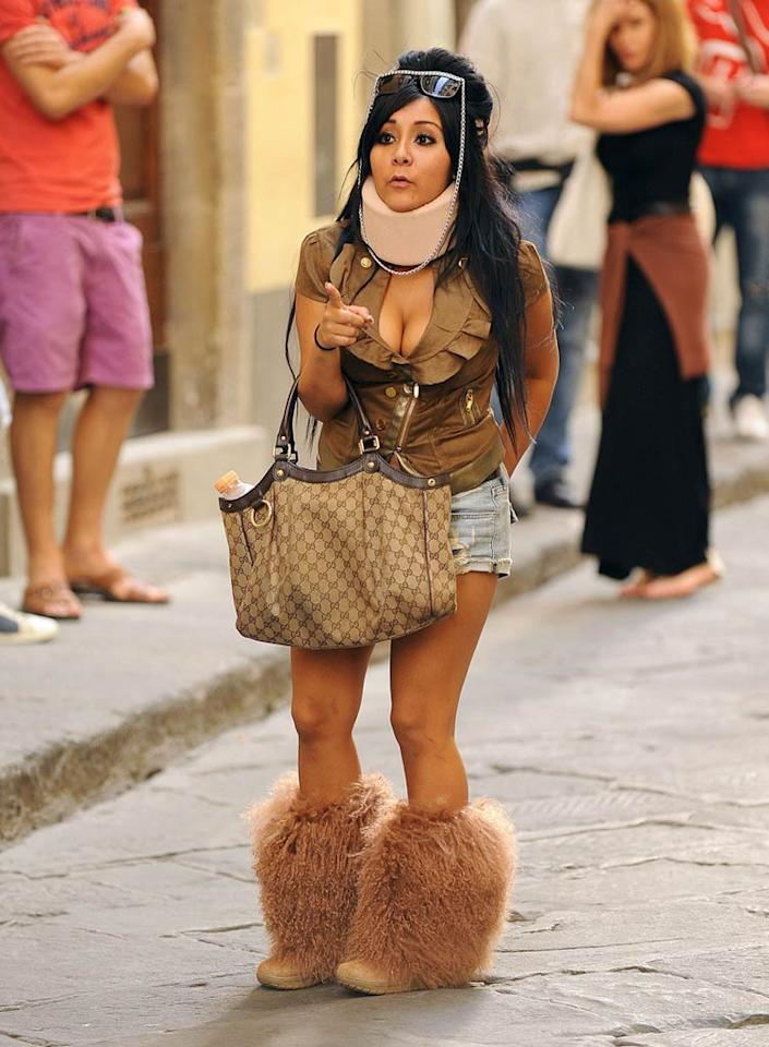 """Following a minor fender bender, in which she rear-ended a police car, fashion-challenged """"Jersey Shore"""" star Snooki hit the streets of Florence, Italy, in a leather top and denim Daisy Dukes. Tacky accessories included a padded neck brace (just for show), a monstrous handbag, and fugly fur booties. Kika Press/<a href=""""http://www.pacificcoastnews.com/"""" target=""""new"""">PacificCoastNews.com</a> - May 31, 2011"""