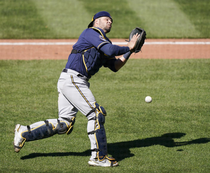 Milwaukee Brewers catcher Manny Pina drops a popup in foul territory by St. Louis Cardinals' Nolan Arenado during the seventh inning of a baseball game Sunday, April 11, 2021, in St. Louis. (AP Photo/Jeff Roberson)