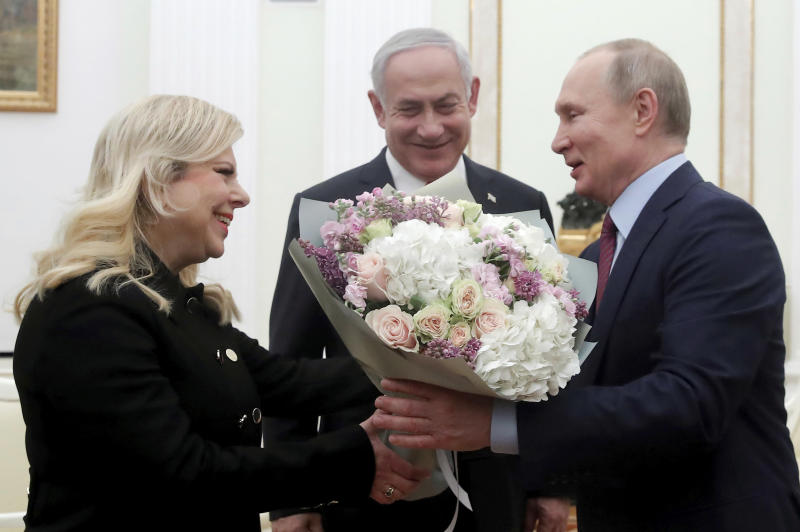 Russian President Vladimir Putin, right, greets Israeli Prime Minister Benjamin Netanyahu's wife Sara, left, as Israeli Prime Minister Benjamin Netanyahu stands at centre, prior to their talks in the Kremlin in Moscow, Russia, Thursday, Jan. 30, 2020. Netanyahu visited Moscow to discuss the U.S. Mideast peace plan with Putin and take an Israeli woman who had been jailed in Russia back home. (Maxim Shemetov/Pool Photo via AP)