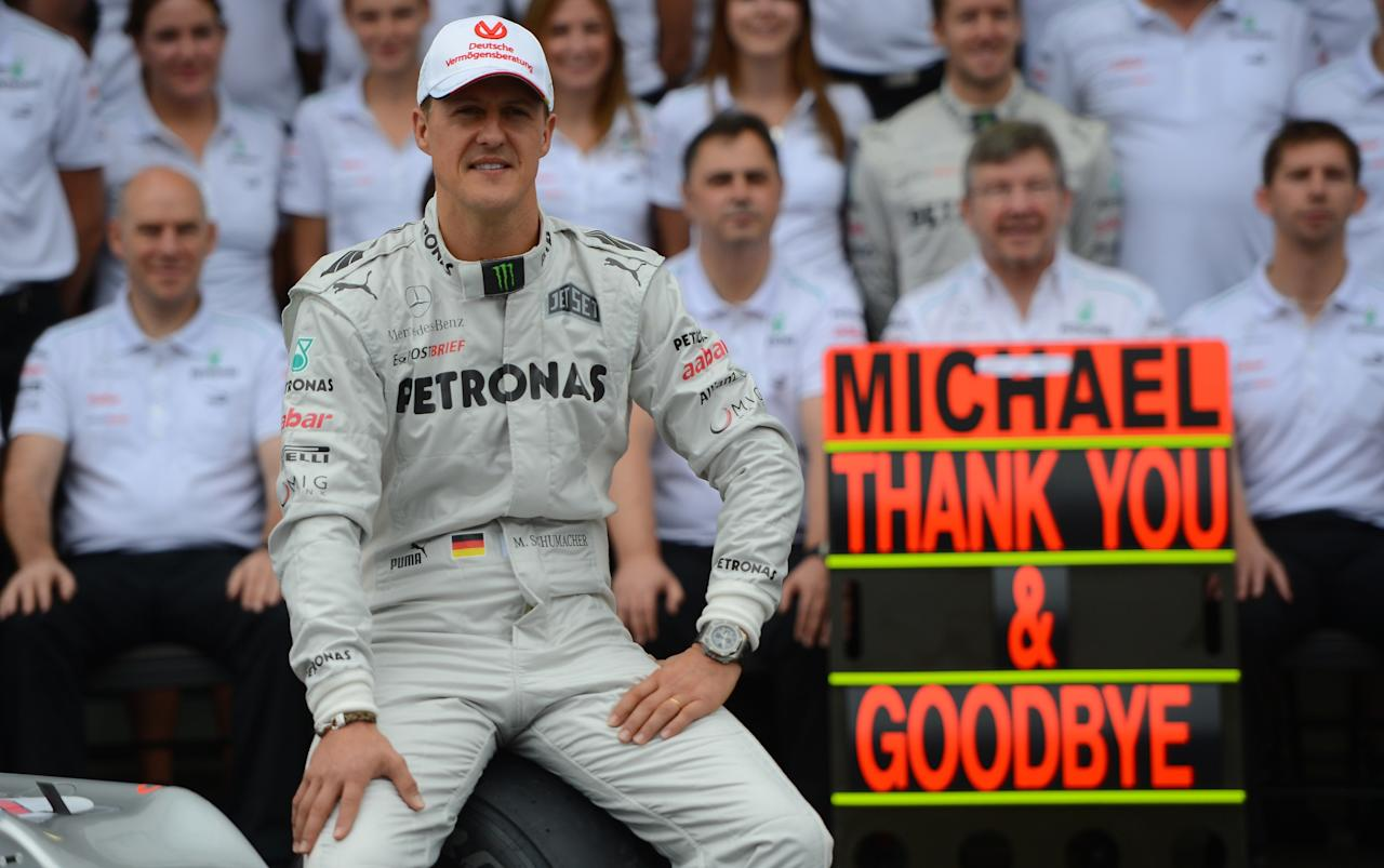 TOPSHOTS  German Formula One driver Michael Schumacher poses with the Mercedes team on November 25 , 2012 in the pits of the Interlagos racetrack in Sao Paulo, Brazil. Michael Schumacher will retire from the F-1 after the Brazilian GP.     AFP PHOTO/YASUYOSHI CHIBAYASUYOSHI CHIBA/AFP/Getty Images