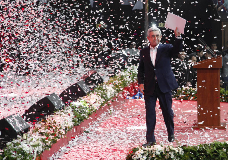 Ticker-tape falls all around as Armenian President Serge Sarkisian is greeted by his supporters during a meeting while campaigning for the vote in Yerevan, Armenia, Friday, Feb. 15, 2013.  President Serge Sarkisian is expected to easily win a second five-year term in Monday's vote. (AP Photo/ Tigran Mehrabyan, PanARMENIAN)