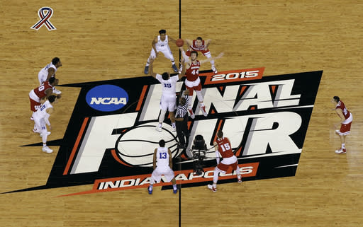 FILE -Duke's Jahlil Okafor (15) and Wisconsin's Frank Kaminsky (44) battle for the ball at the tip off during the first half of the NCAA Final Four college basketball tournament championship game in Indianapolis, in this Monday, April 6, 2015, file photo. The NCAA announced Monday, Jan. 4, 2021, that all 67 men's basketball tournament games including the Final Four will be played entirely in Indiana in a bid to keep the marquee event from being called off for a second consecutive year because of the coronavirus pandemic.(AP Photo/David J. Phillip, File)