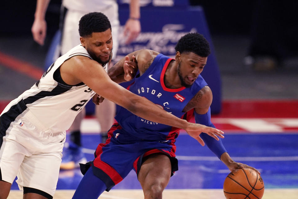San Antonio Spurs forward Rudy Gay (22) and Detroit Pistons guard Josh Jackson (20) reach for the loose ball during the second half of an NBA basketball game, Monday, March 15, 2021, in Detroit. (AP Photo/Carlos Osorio)