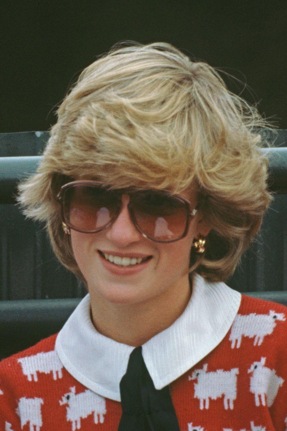 <p>At a polo match wearing the iconic sheep sweater with her hair blown out away from her face.</p>