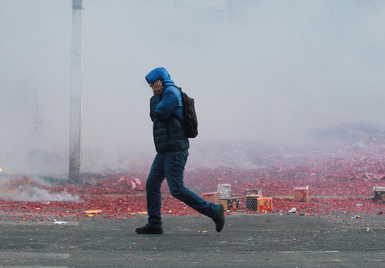 A man walks past a street amid heavy smog as shop owners set off firecrackers and fireworks to pray for good business, after Spring Festival holidays, in Harbin, Heilongjiang province, China February 23, 2018. REUTERS/Stringer ATTENTION EDITORS - THIS IMAGE WAS PROVIDED BY A THIRD PARTY. CHINA OUT.