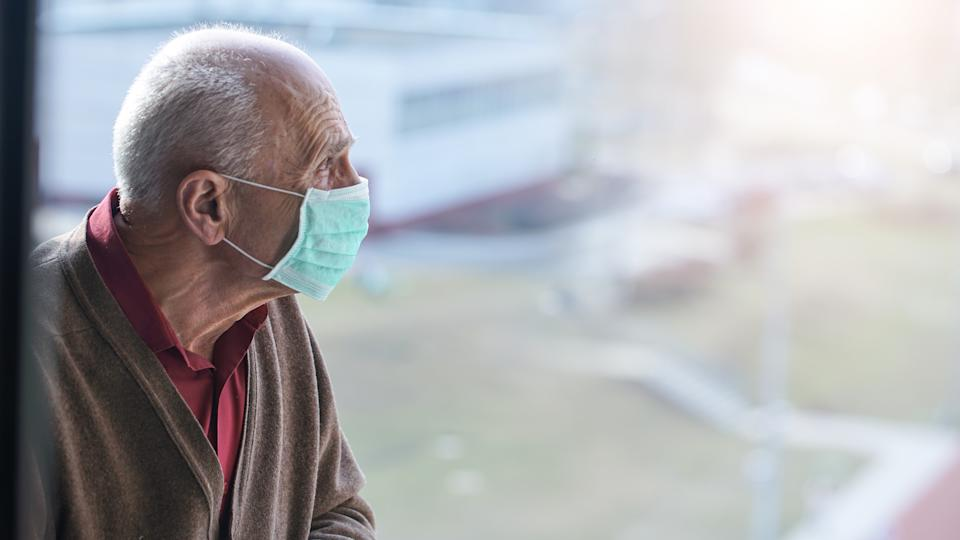 aged pensioner man with gray hair wearing medical facemask looking through window health care concept
