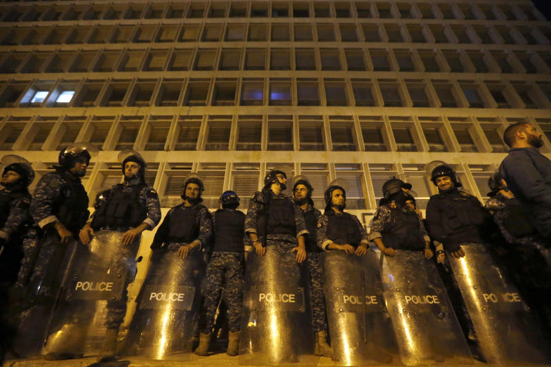 Riot police stand guard during ongoing protests against the Lebanese government, in front of the Central Bank, in Beirut, Lebanon, Thursday, Nov. 28, 2019. Lebanon paid back a Eurobond worth $1.5 billion that was scheduled to mature Thursday, a Finance Ministry official said, pacifying concerns of a first-ever default on its debt amid the worst financial crisis in three decades. (AP Photo/Bilal Hussein)
