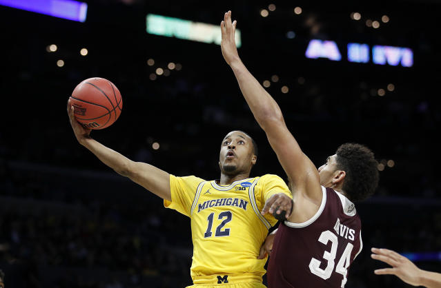 Michigan guard Muhammad-Ali Abdur-Rahkman (12) shoots as Texas A&M center Tyler Davis (34) defends during the first half of an NCAA men's college basketball tournament regional semifinal Thursday, March 22, 2018, in Los Angeles. (AP Photo/Jae Hong)