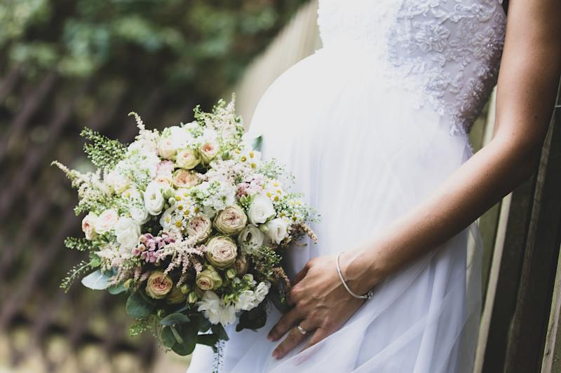 Expecting bride with a beautiful wedding bouquet