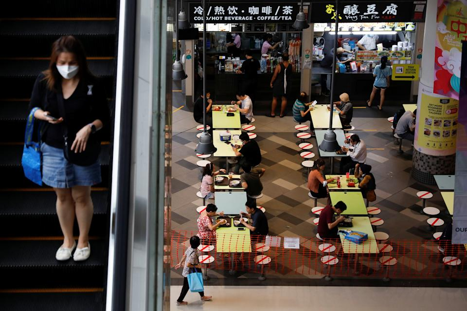 People dine in groups of two at a mall as restrictions on social gathering are tightened due to the surge of cases in the coronavirus disease (COVID-19) outbreak, in Singapore, September 29, 2021. REUTERS/Edgar Su