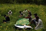 Relatives sit next to the body of a man, who died due to the coronavirus disease (COVID-19), as they wait for a grave to be prepared for his burial at a graveyard on the outskirts of Srinagar