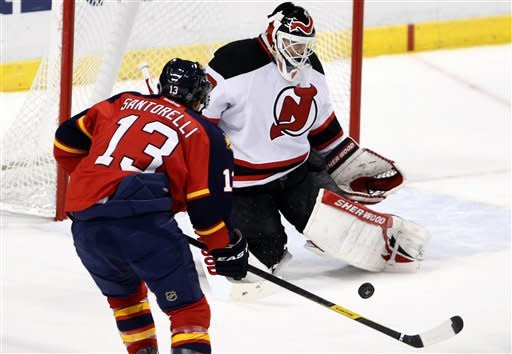 Florida Panthers center Mike Santorelli (13) attempts a shot on New Jersey Devils goalie Martin Brodeur during the first period of an NHL hockey game, Tuesday, Dec. 13, 2011, in Sunrise, Fla. (AP Photo/Wilfredo Lee)
